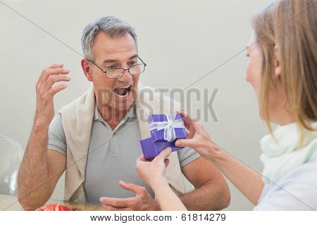 Shocked man receiving a gift by woman at home
