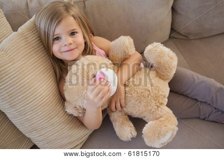 High angle portrait of a young smiling girl with stuffed toy sitting on sofa in the living room at home
