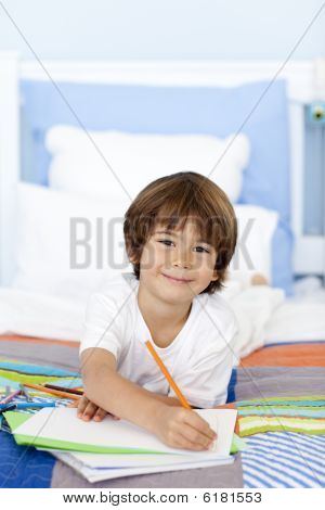 Smiling Little Boy Drawing In Bed