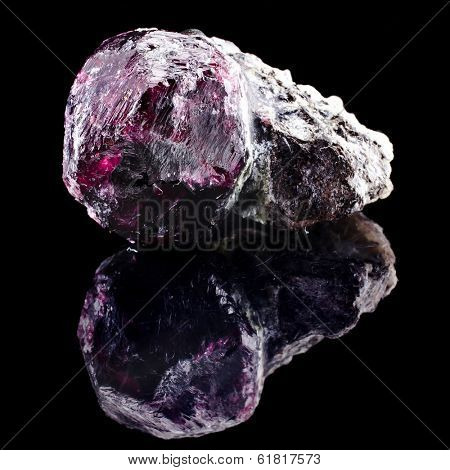 Natural Uncut Raw Ruby with reflection on black surface background