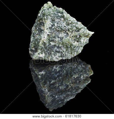 mineral Olivine with reflection on black surface background