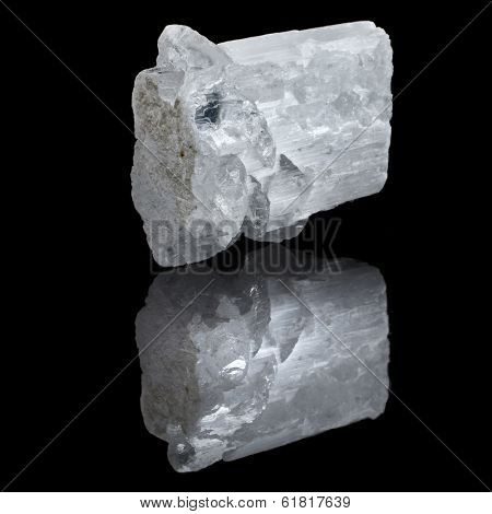 White Selenite mineral with reflection on black surface background
