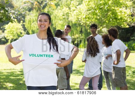 Happy female volunteer holding tshirt with friends disucssing in background