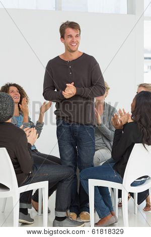 Rehab group applauding happy man standing up at therapy session