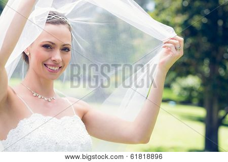Portrait of happy young bride unveiling self in garden