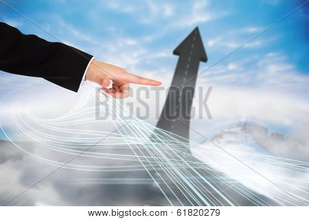 Digital composite of finger pointing to road turning into arrow