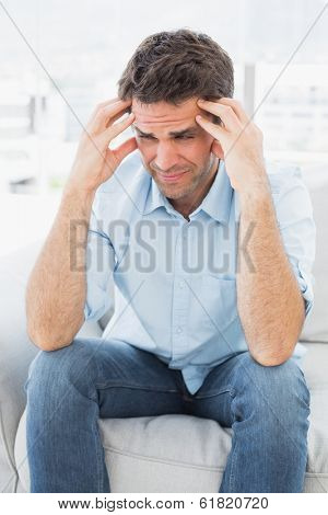 Grimacing man sitting on the couch with a headache at home in the living room