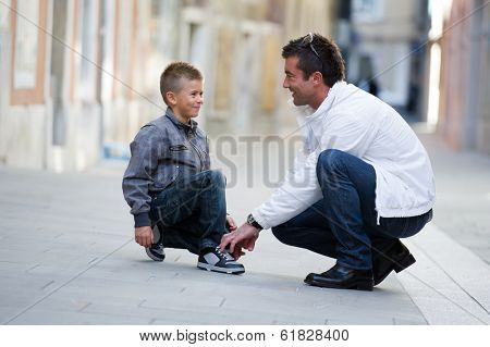 Father helping her son to tie his shoes
