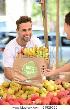 Greengrocer owner of a small business selling fruits and vegetables to a woman carrying a shopping paper bag with a 100% organic certified label.