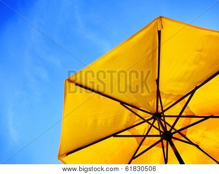 Yellow umbrella and blue sky symbolizing vacationing in summer