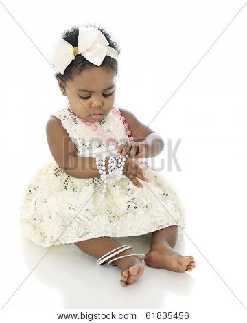 A beautiful baby girl all dressed up, examining the bracelet of beads she wears on her wrist.  On a white background.