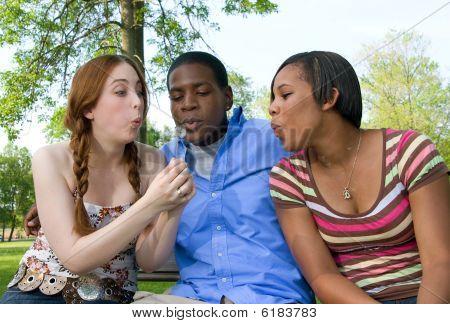 Tres amigos adolescentes que sopla sobre el diente de León