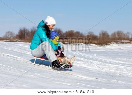 Mom And Daughter Ridding On Sledge