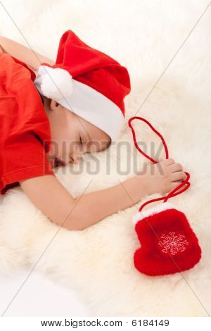 Boy Sleeping And Dreaming About Gifts In Christmas Sock
