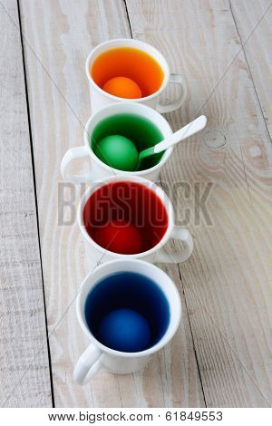 High angle view of four cups with dye for Easter eggs. The cups are filled with of yellow, blue, red and green dye. There are eggs in each cup on a rustic farmhouse style kitchen table.