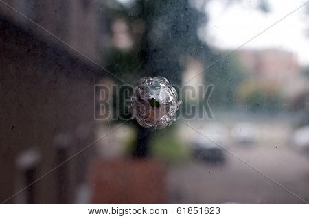 Bullet hole on the dirty glass background.