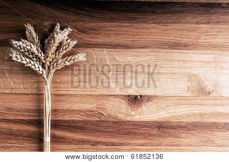 Bundle Of Wheat On Wooden Background.