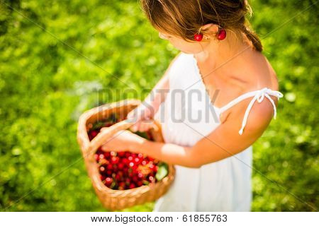 Beautiful young woman holding a basket filled with freshly picked cherries