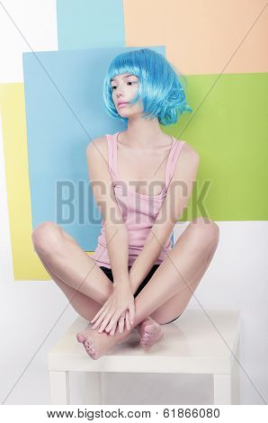 Patchwork. Funky Girl In Azure Wig Sitting In Studio On White Chair