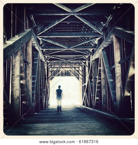 Woman walking towards the sunlight from a covered bridge. Filtered to look like an aged instant photo.