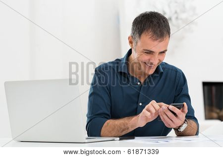 Smiling Mature Man In Front Of Laptop Using Cellphone