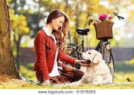Beautiful female sitting on a green grass and looking at her labrador retriever dog in a park