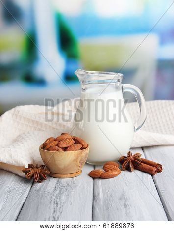 Almond milk in jug with almonds in bowl, on color wooden table, on bright background
