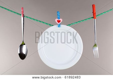 Tableware dried on rope on grey background