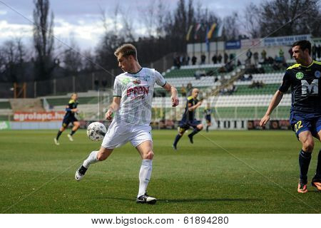 KAPOSVAR, HUNGARY - MARCH 16, 2014: Kink Tarmo (with ball) in action at a Hungarian Championship soccer game - Kaposvar (white) vs Puskas Akademia (blue).