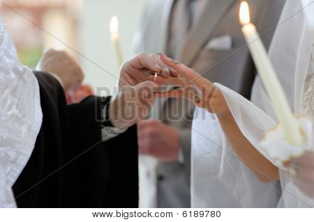 Priest Putting The Ring On Bride's Finger