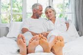 stock photo of legs apart  - Portrait of a happy mature couple sitting in bed at home - JPG
