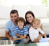 stock photo of happy family  - Portrait of happy family smiling at the camera in living - JPG