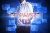 Businessman presenting the word spyware against futuristic blue screens