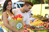 Happy couple shopping fruits and vegetables at a open street market, carrying a shopping paper bag w