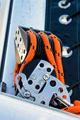 foto of pulley  - Pulleys with orange ropes and stainless steel buckles on a sailing yacht - JPG