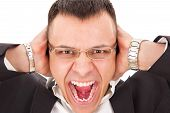 stock photo of yell  - furious man with glasses yelling holding hands on his ears - JPG