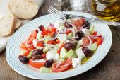 foto of greek food  - Greek salad in white plate on a wooden table - JPG