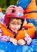 Happy little girl wearing helmet sitting in a rafting boat