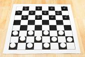 stock photo of draught-board  - Starting position on vinyl 8x8 checkers board on wooden table - JPG