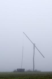 foto of shadoof  - Shadoof in grey fog at early morning  - JPG