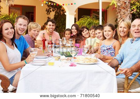 Large Family Group Enjoying Meal On Terrace Together