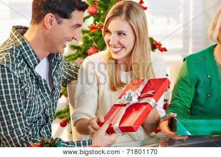 Happy smiling couple exchanging gifts at christmas eve