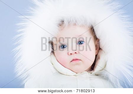 Sweet Baby In A White Snow Suit With A Fur Hood Looking Tired