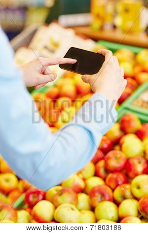 Hand scanning information of fresh fruit with a smartphone in a supermarket