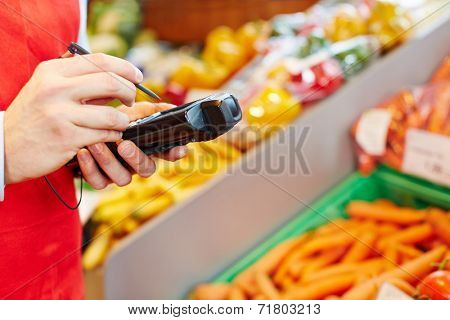 Hand holding mobile data registration terminal in a supermarket