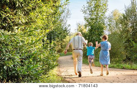 Grandparents and grandchild jumping outdoors