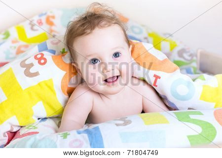 Funny Little Baby Playing Peek-a-boo Under A Colorful Blanket