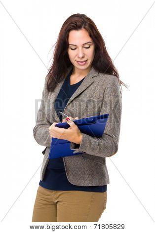 Brunette woman wite on clipboard