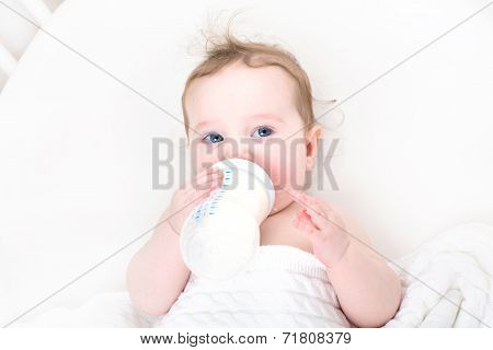 Little Baby Drinking Milk From A Bottle In A White Crib