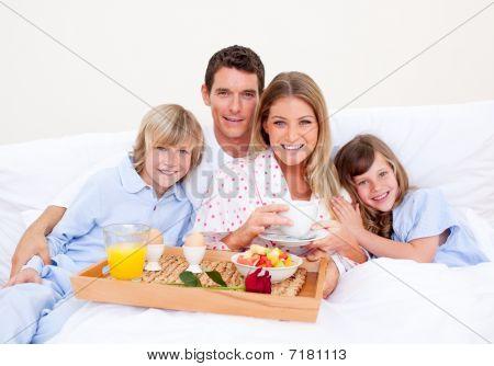 Família sorridente, café da manhã sentado na cama